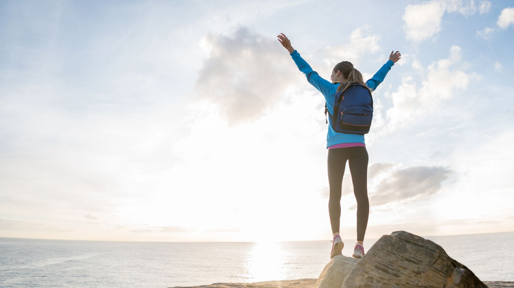 Woman stands proudly after a hike to the coastline at Montana de Oro State Park in Los Osos